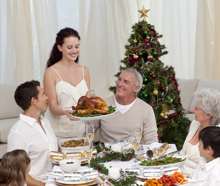 Woman showing turkey to her family for Christmas photo