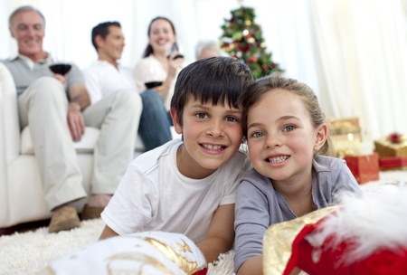 Children lying on floor with their family in Christmas Stock Photo - 10095195