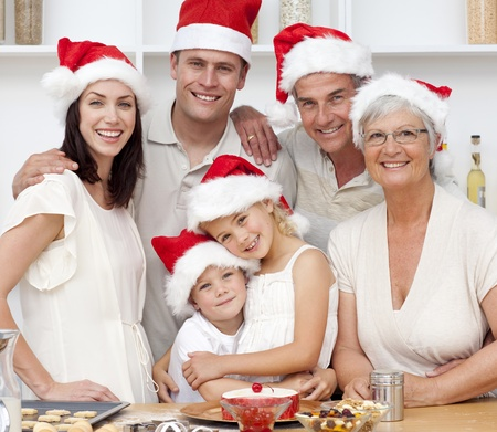 Smiling family baking Christmas cakes photo