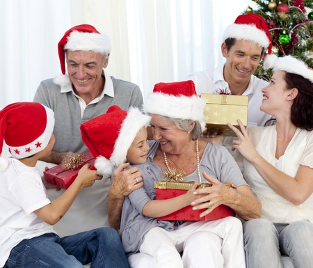 Laughing family at Christmas time giving presents photo