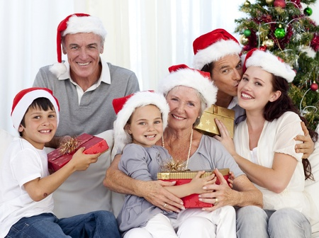 Smiling family at Christmas time giving presents photo