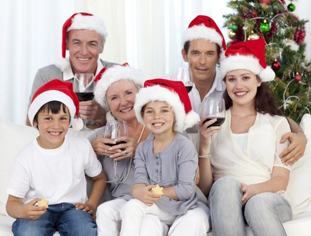 Family celebrating Christmas with wine and sweets photo