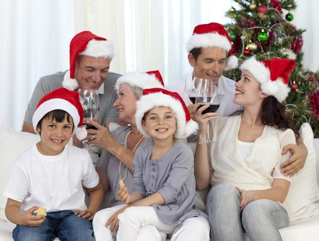 Family celebrating Christmas with wine and sweets at home photo
