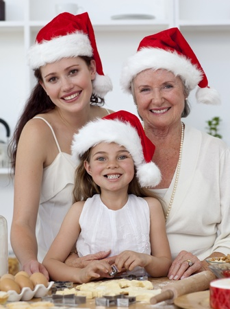 Daughter, mother and grandmother baking Christmas sweets photo
