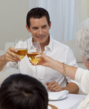 Man toasting with his mother in a Christmas dinner photo
