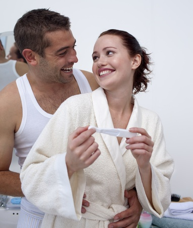 prueba de embarazo: Pareja feliz en el baño con una prueba de embarazo