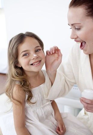 Happy mother putting cream on her daughters face photo