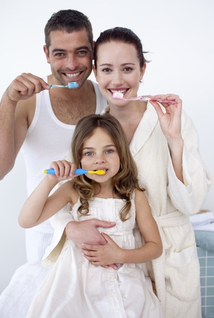 Parents and daughter cleaning their teeth in bathroom photo