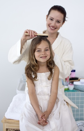 Mother doing her daughter's hair Stock Photo - 10092230