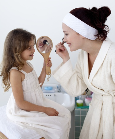 Daughter helping her mother in makeup photo
