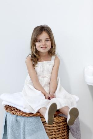 Little girl sitting in bathroom photo