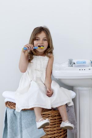 Daughter cleaning her teeth in bathroom photo