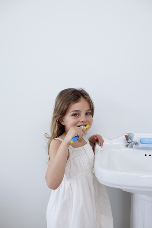 Little girl cleaning her teeth in bathroom with copy-space photo