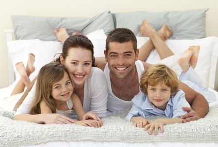 Gelukkig gezin in bed liggen en lachen naar de camera Stockfoto