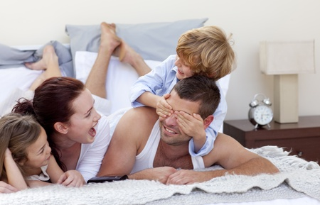 Happy young family having fun in bed photo