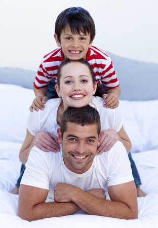Happy parents and son playing in bed photo
