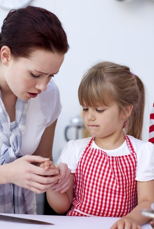 injure: Little girl injured by a knife in kitchen Stock Photo