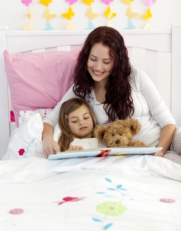 Mother and daughter reading in bedroom photo