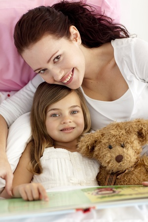 Portrait of mother and daughter reading in bed Stock Photo - 10108560