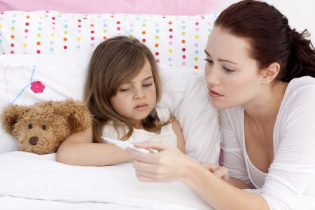 sick girl: Mother taking sick daughters temperature