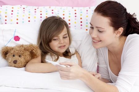fiebre: Madre tomando la temperatura de su hija