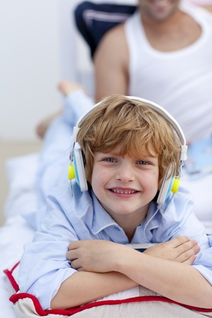Portrait of a little boy listening to music in bedroom photo