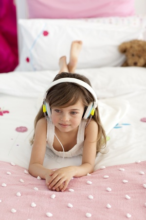 Cute girl listening to the music in bed photo
