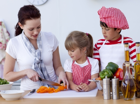 Children helping mother cooking in the kitchen photo