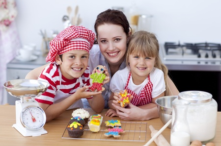 Mother baking with children in the kitchen photo