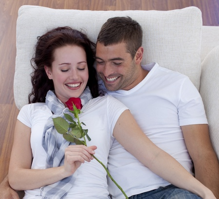 Portrait of lovers on sofa with a rose Stock Photo - 10091837