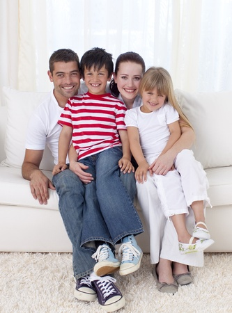Family sitting on sofa together photo