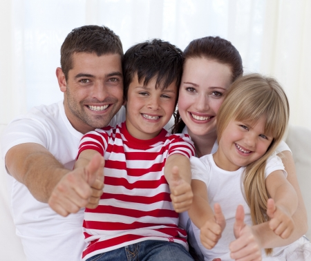 family on couch: Family sitting on sofa with thumbs up