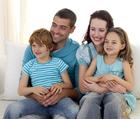 Family sitting on sofa watching television photo