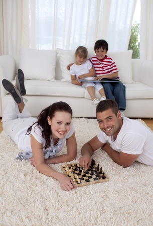 Couple playing chess on floor in living-room Stock Photo - 10095282