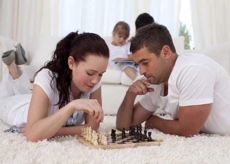 Parents playing chess on floor in living-room photo