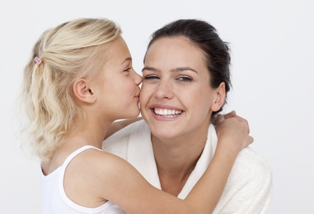 Daughter kissing her mother in bathroom photo