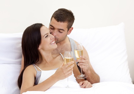 Lovers drinking champagne in bed photo