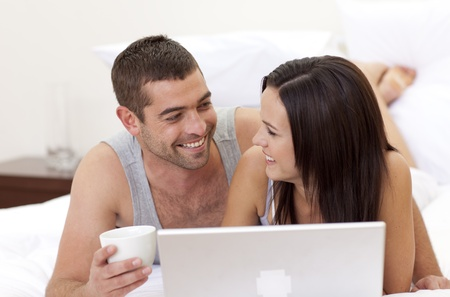Husband and wife in bed using a laptop Stock Photo - 10093413