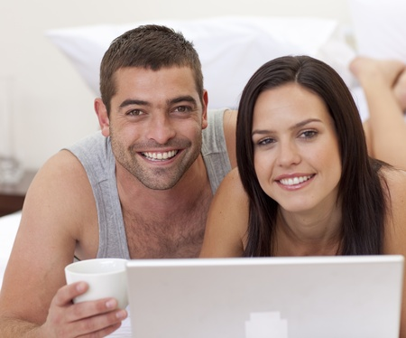 Portrait of couple in bed using a laptop Stock Photo - 10094461