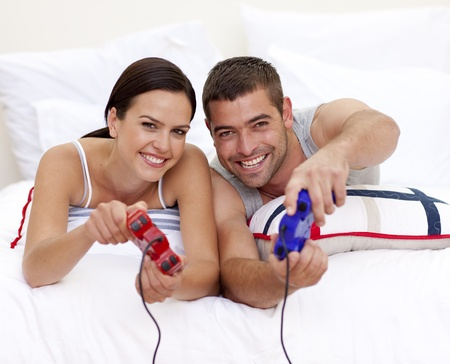 Couple having fun playing videogames in bed photo