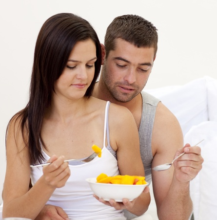 roomservice: Young couple eating fruit in bed