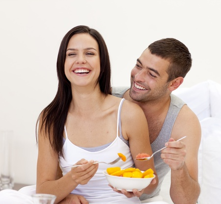 Smiling couple having nutritive breakfast in bed photo