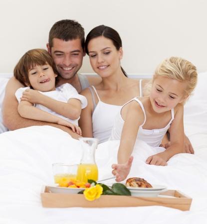 Familia feliz tomando el desayuno en la habitaci�n Foto de archivo - 10091572