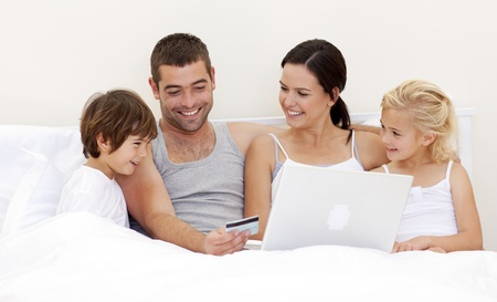 Familia de comprar en línea en la cama