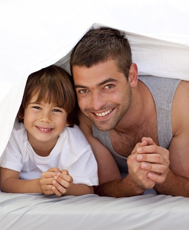 Father and son together under the bedsheets Stock Photo