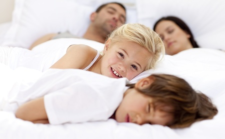 Smiling daughter relaxing with her brother and parents in bed photo