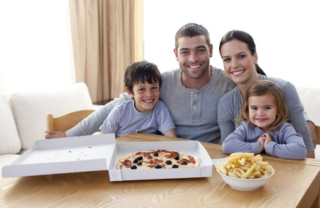 mealtime: Family eating pizza and fries at home Stock Photo