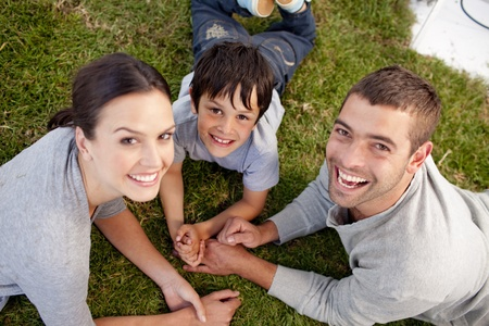 familia en jardin: Los padres y el ni�o acostado en el jard�n