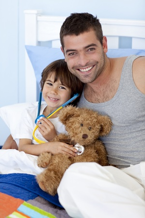Father and son playing doctors in bed photo