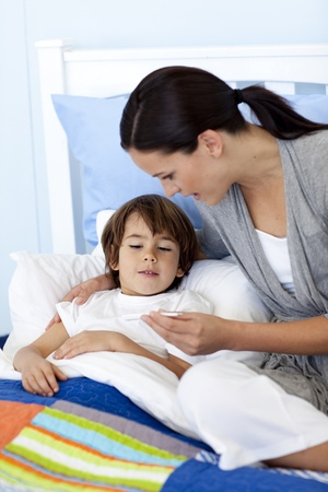 sick day: Mother taking her sons temperature